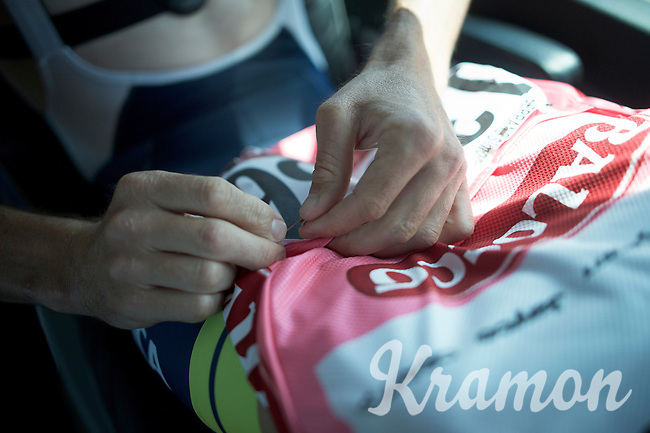 Simon Gerrans (AUS/Orica-GreenEDGE) pins on his race number on his 'maglia rosa' at the start of stage 2 on the teambus<br /> <br /> 2015 Giro<br /> stage 2: Albenga - Genova (177km)