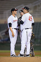 Kannapolis Intimidators pitching coach Brian Drahman (45) has a chat on the mound with relief pitcher Yelmison Peralta (28) and catcher Casey Schroeder (10) during the game against the Hickory Crawdads at Kannapolis Intimidators Stadium on April 9, 2016 in Kannapolis, North Carolina.  The Crawdads defeated the Intimidators 6-1 in 10 innings.  (Brian Westerholt/Four Seam Images)