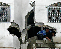 "Palestinain fixing his house  after isreal withdrawal from gaza strip.March.03.2008.""phto by Fady Adwan"""