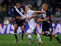 Wayne Rooney (10) of England is squeezed out by Ricardo Clark (13) and Jay DeMerit (15) of USA. USA vs England in the 2010 FIFA World Cup at Royal Bafokeng Stadium in Rustenburg, South Africa on June 12, 2010.