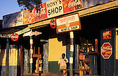 Lolgorian, Kenya. High street scene; shops with advertisements for Fanta, Coca-Cola, Sportsman cigarettes, Hedex painkillers.