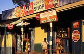 Lolgorian, Kenya. High street scene; shops with advertisements for Fanta, Coca-Cola, Sportsman cigarettes, Hedex painkillers.