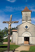 Facade of a church with Jesus Christ on a cross in the foreground, Mano, Landes, France.