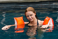 Woman in pool wearing water wings