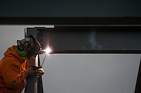 Steelworker welds sections of a beam at Northstar Cafe.