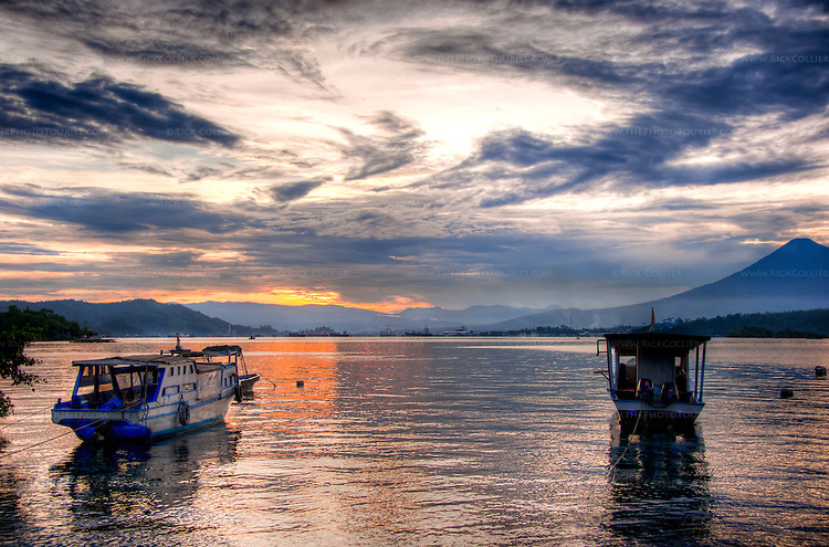 Moored dive boats frame the sunset view, looking west across the Lembeh Strait to Bitung and North Sulawesi from the Lembeh Resort.  (HDR image)
