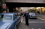City of London, a tramp begging money from the driver of a Rolls Royce at London Bridge. Rich poor contrasting way of life. 1992 1990s UK.
