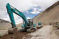 "The road to Everest base camp.<br /> China started building a controversial 67-mile ""paved highway fenced with undulating guardrails"" to Mount Qomolangma, known in the west as Mount Everest, to help facilitate next year's Olympic Games torch relay./// A digger and steam roller building the road just a couple kilometers from EBC.<br /> Tibet, China.<br /> July, 2007"