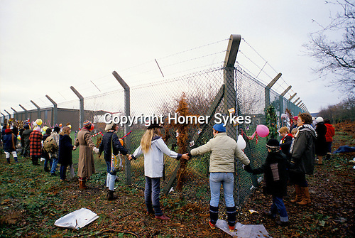 Greenham Womens Peace Camp  blockade of American USAF nuclear cruise missile air base at Greenham Common Berkshire  England 1983. Women holding hands encircle  the outer perimeter fence of the  military base. This was celebrated and called  'Embrace the Base'.