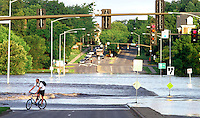 """Bill Gaul, Iowa State University graduate student from Des Moines, turns back from flood water covering the intersection of Lincoln Way and University Blvd. Werdnesday morning in Ames.  """"I guess I won't be going to campus today,"""" he said.   Flooding in Ames, Iowa Wednesday, August 11, 2010 from the flooded South Skunk River and Squaw Creek."""
