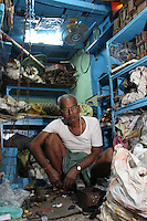 A man sits in his store in the Chandni Chowk electronics market in Kolkata, India. November, 2013