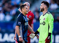 """CARSON, CA - FEBRUARY 15: Javier """"Chicharito"""" Hernandez #14 of the Los Angeles Galaxy and Quentin Westberg #16 of Toronto FC have a laugh during a game between Toronto FC and Los Angeles Galaxy at Dignity Health Sports Park on February 15, 2020 in Carson, California."""