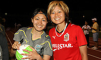Japanese players, Karina Maruyama (11) of the Philadelphia Independence, and Mami Yamaguchi (9) of the Atlanta Beat, sign autographs for fans after the game. Atlanta and Philadelphia played to a 0-0 draw in the season opener for both teams at John A Farrell Stadium in West Chester, PA.