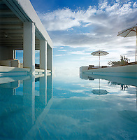 View over the water of an infinity pool out to a summer sky with scattered white cloud