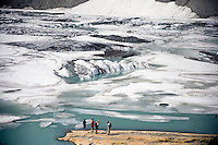 Hikers stand at the base of Grinnell Glacier in Glacier National Park in Montana.  The water is from the melting glacier.  Scientists predict that if current global warming trends continue, many of the the park's glaciers will disappear.