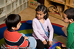 Education preschoool children ages 3-5 pretend play two boys and a girl playing together  talking to each other horizontal