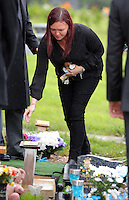 Pictured: A woman leaves flowers after the burial at Thornhill Cemetery, Cardiff, Wales, UK. Tuesday 28 June 2016<br /> Re: The funeral of Sion, the baby boy found dead in the River Taff in Cardiff has taken place<br /> Generous locals raised nearly £1,400 for the memorial after reading about plans to hold a fitting ceremony for the newborn baby whose body was discovered in Cardiff a year ago.<br /> The funeral took place at the Briwnant Chapel at Thornhill Crematorium, Cardiff. Members of the public are invited to be among the congregation.