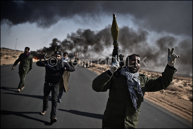 © Remi OCHLIK/IP3 -   RAS LANOUF March 11, 2011 - A group of opposition fighter goes to the frontline, armed with RPG, and doing the victory sign. ..Opposition forces fight troops of colonel Muamar Gadhafi on a road just outside the strategic oil town of Ras Lanouf, Libya..Loyalist forces bombed the rebels from the air and the ground. At least five oppositin fighters were killed and fifteen injured