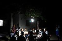 SYRIEN, 08.2014, Koreen (Provinz Idlib). Leben ohne Zentralregierung: Maenner eines Wohnviertels geniessen den lauen Sommerabend auf der Strasse im Licht einer im Baum aufgehaengten solar-geladenen LED-Lampe. | Life without a central government: Several men of a neighbourhood sit together outside in the street to enjoy the summer evening chatting under a solar-charged LED-light hanging in the tree.<br /> © Timo Vogt/EST&OST
