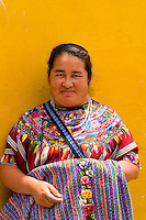 Local colorful woman against bright wall with local print dress portrait in tourist village of Antigua Guatemal
