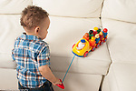 12 month old baby boy pulling string on toy bus to move it closer
