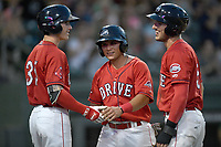 Shortstop Frankie Rios (12) of the Greenville Drive is congratulated by Jarren Duran (35), left, and Jordan Wren (5) after both scored in the second inning of a game against the Lexington Legends on Saturday, September 1, 2018, at Fluor Field at the West End in Greenville, South Carolina. Greenville won, 9-6. (Tom Priddy/Four Seam Images)