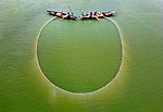 """Pictured: Fishermen using traditional way with a large net being pulled together between them in two small boats, while hitting the surface of the water to avoid loosing fish.<br /> <br /> Photographer, Abdul Momin, 29, spotted the men fishing the Brahmaputra river in Gaibandha, Bangladesh.<br /> <br /> He said, """"They usually catch small fishes like barbs, dwarf catfish, spotted sneakhead, stinging catfish, stripped gouromi, potasi and bata labeo.  First they spread the net in a vast area of up to five acres then they pull the net gently from both ends so they surround the fish making them unable to escape.""""<br /> <br /> """"It's very time consuming and laborious work. It takes about an hour for every sesson. They catch between 8 to 10kg of small fish each time and can do this up to five times a day. Big fish usually jump and manage to escape the net.""""<br /> <br /> """"When the boats get close enough they strike the water using sticks so that fish can't escape through the small gap between the boats.""""<br /> <br /> """"The shape of the net depends on the number of boats, if they use two boats then the shape is spherical, if three are used it's more triangular, with a fouth making a rectangular shape.""""<br /> <br /> Please byline: Abdul Momin/Solent News<br /> <br /> © Abdul Momin/Solent News & Photo Agency<br /> UK +44 (0) 2380 458800"""