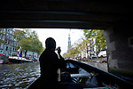 A woman takes a picture from a small boat while exploring the canals of Amsterdam.