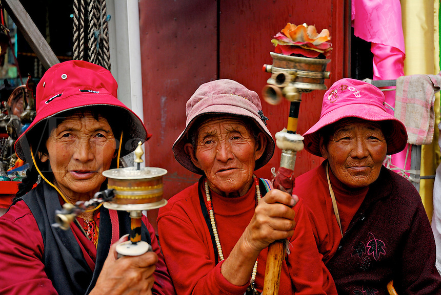 Tibetan Buddhist pilgrims, with prayer wheels and rosaries, taking a rest while circumambulating the Barkhor circuit around the Jokhang Temple during Saga Dawa festival, Lhasa, Tibet.
