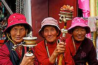Tibetan Buddhist pilgrims, with prayer wheels and rosaries, taking a rest while circumambulating the Barkhor circuit around the Jokhang Temple during Saga Dawa festival, Lhasa, Tibet.