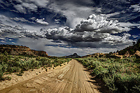 A BLM road in the Rio Puerco Valley with dark, stormy clouds dropping rain over Cabezon Peak in the distance.