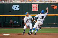 UCLA shortstop Pat Valaika (10) and second baseman Cody Regis (18) attempt to field a bad hop ground ball during Game 12 of the 2013 Men's College World Series against the North Carolina Tar Heels on June 21, 2013 at TD Ameritrade Park in Omaha, Nebraska. The Bruins defeated the Tar Heels 4-1, to reach the CWS Final and eliminate North Carolina from the tournament. (Andrew Woolley/Four Seam Images)