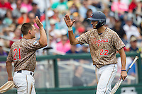 Virginia Cavaliers shortstop Daniel Pinero (22) is greeted by teammate Matt Thaiss (21) after scoring against the Arkansas Razorbacks in Game 1 of the NCAA College World Series on June 13, 2015 at TD Ameritrade Park in Omaha, Nebraska. Virginia defeated Arkansas 5-3. (Andrew Woolley/Four Seam Images)