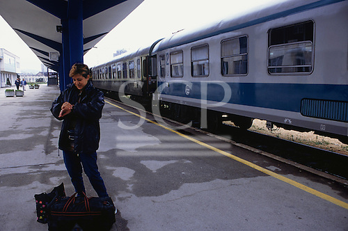 Sarajevo, Bosnia and Herzegovina. People standing on the platform; train on the Sarajevo - Zagreb route; woman looking at her watch.