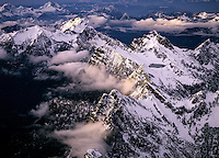 Aerial of rugged mountain peaks & Crater Lake highlighted by  setting sunlight in the North Cascades Mountain Range, Washington State. Notable peaks from center bottom to center top include: Sheep Gap Mountain, North Peak, Gothic Peak, Sperry Peak.