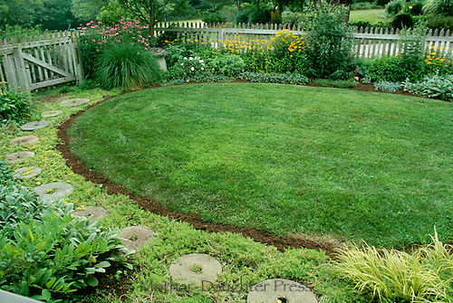 Round front yard garden with decorative stepping stones and blooming flowers, Missouri USA