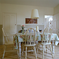 A floral oil cloth covers the table in this Swedish-style country dining room