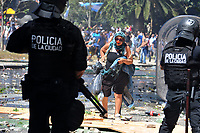 A woman crosses Congress square in the middle of severe riots  while the Congress was discussing modifications in a  retirement law.