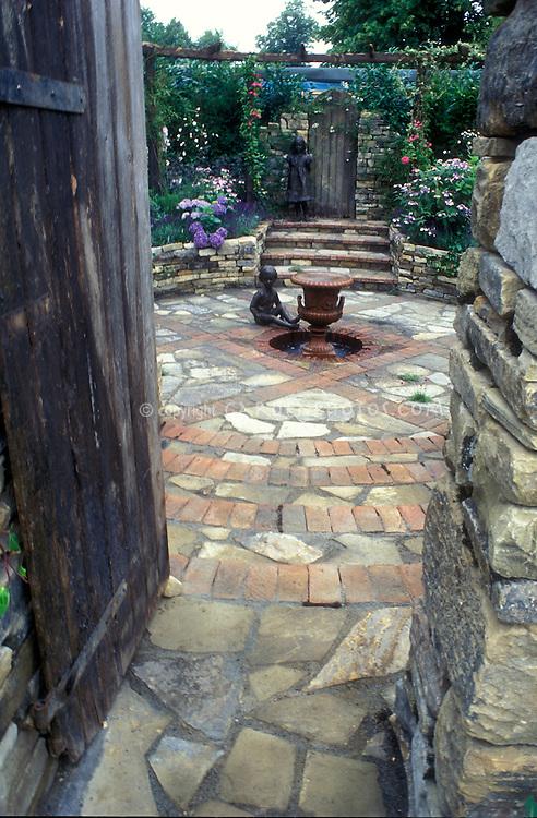 Secret garden with brick and stone pavers, behind door, with child statues 4125 . Board and batten door