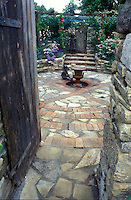 Secret garden with brick and stone pavers, behind door, with child statues 4125 . Board and batten door