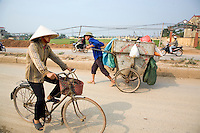 Vietnam. Ha Tay province. Lai Xa. A local worker of the village's cooperative running the collection and the waste disposal service, walks on the road  with his rubbish cart. The local project committee is in charge at a local level of a flexible decentralized community sanitation project (solid waste and small-scale waste water management in a system based on houselhold participation and community involvement, as a decentralized sanitation implementation). Waste collection is an important requisite to prevent rubbish from clogging the new drainage and sewage system. Vietnamese hat. Lai Xa is a typical hamlet (village) of the Red River delta region and is part of the Kim Chung commune located 15 km west of Hanoi. The peri-urban location is under increasing pressure of urbanization. 07.04.09  © 2009 Didier Ruef