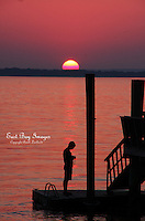 Silhouette of a man in front of a beautiful, pink Narragansett Bay sunset.