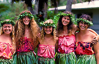 Five smiling women from a haole hula troupe wearing traditional kahiko costumes and haku leis pose with their arms around each other.