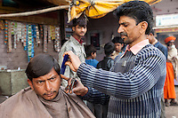 Agra, India.  Streetside Barber Cutting a Customer's Hair.