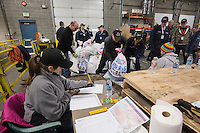 Colleen Dye writes weights down as a crew of volunteers, including a group from the Alaska Military Youth Academy, move, weigh and stack thousands of musher food drop bags that are headed to the 22 checkpoints along the trail at the Airland Transport facility in Anchorage, Alaska on Wednesday, February 17, 2016 just prior to Iditarod 2016