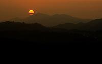 The setting sun turns the entire sky a brilliant orange as it sets behind North Carolina's Blue Ridge Mountains.