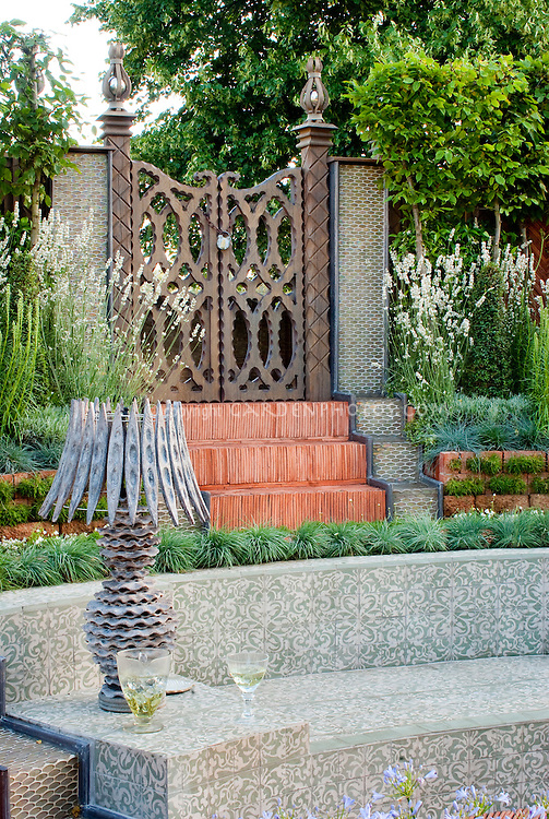 Tiled garden bench surrounds a sunken deck, with beautiful Moorish style landscaping, with garden lamp to create outdoor room feeling, Agapanthus blue flowered bulbs, ornamental grasses, etc, in several levels, outdoor room