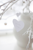 """A paper heart cut-out, with the line """"you are sweet"""", hangs on a white-painted branch"""