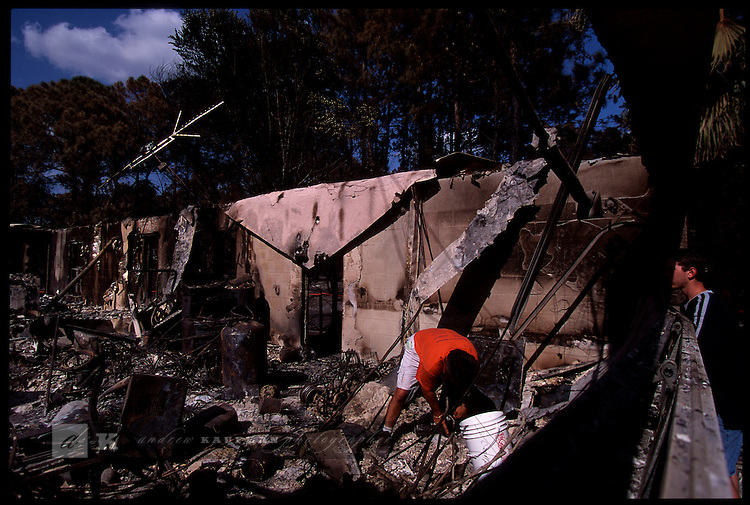 4-21-01.Ray Delfa of North Port, Florida rumages through what is left of his house that was ravaged by wildfires.
