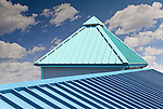 Blue and green metal roof with interesting lines, sunny skies and broken white cumulus clouds.